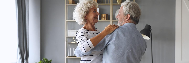 Een ouder stel danst in de woonkamer