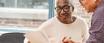Man helpt oudere vrouw met papieren