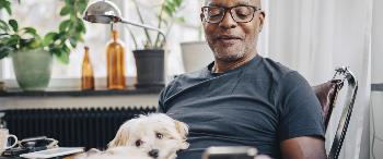 Man met hond op schoot kijkt op mobiel
