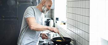 Een man bezig met bewust eten in de keuken.