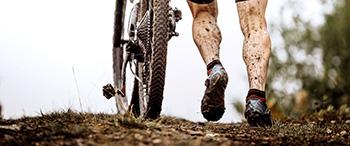 Fietser loopt naast fiets door de modder