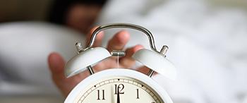Persoon in bed zet wekker uit