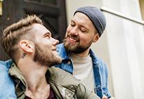 Twee mannen glimlachen met arm om elkaar