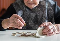 Oude vrouw stopt muntgeld in portemonnee