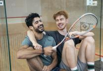 2 lachende vrienden rusten uit na het sporten