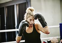 Vrouw met bokshandschoenen aan