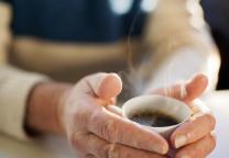 Handen om een warme kop koffie heen
