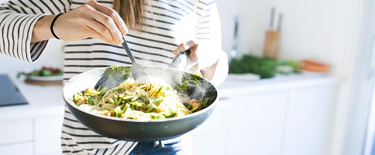 Vrouw in keuken schept gerecht uit pan