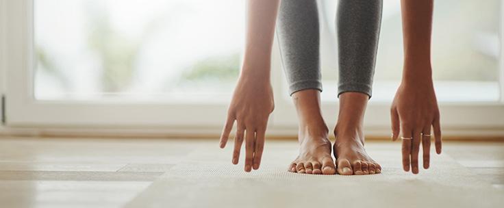 Dame op yogamat buigt voorover