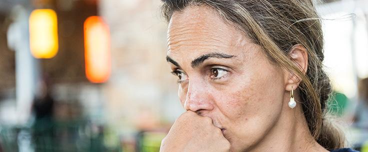 Vrouw kijkt serieus en houdt hand voor haar mond