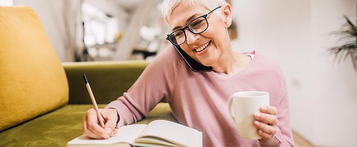 Vrouw schrijft met telefoon tussen schouder en oor