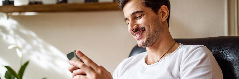 Man kijkt op zijn mobiel