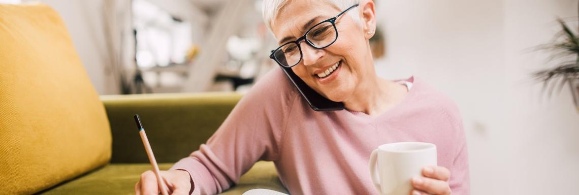 Lachende vrouw belt en schrijft met een koffie erbij