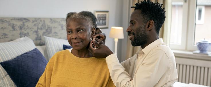 Man helpt vrouw bij indoen van oorbellen