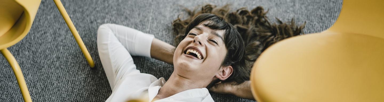 Lachende vrouw ligt op de grond