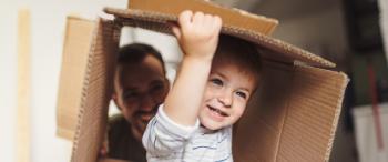 Kleine jongen speelt met kartonnen doos