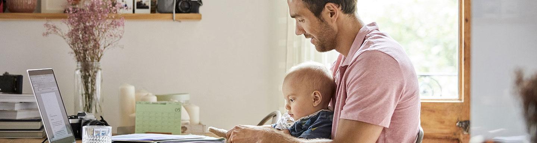 man achter laptop met baby op schoot